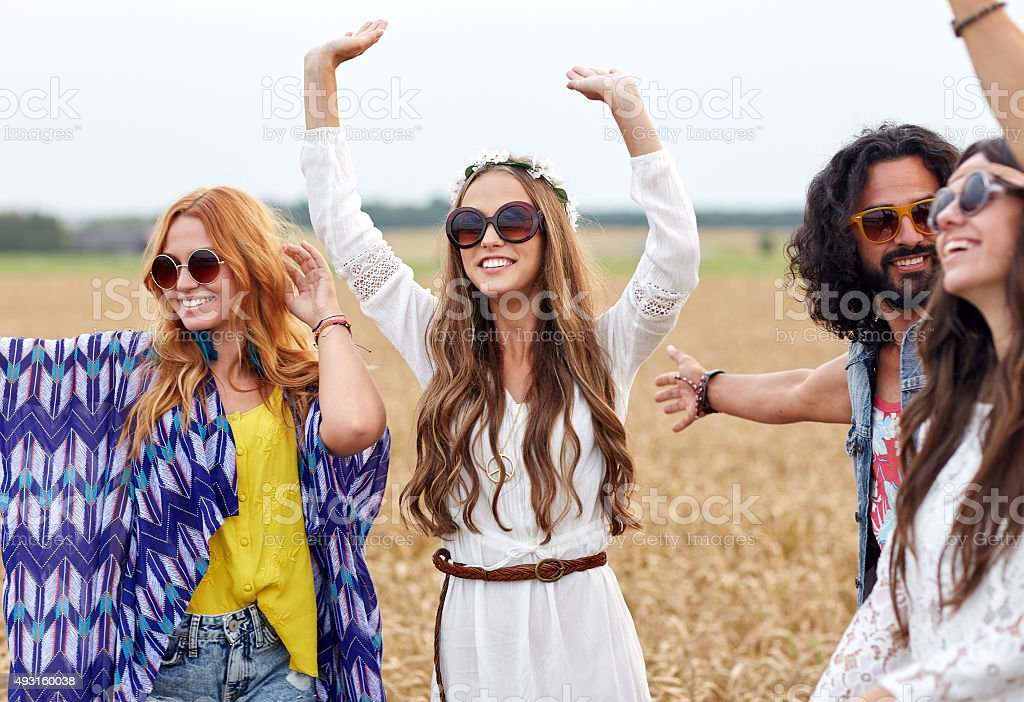 happy young hippie friends dancing on cereal field stock photo