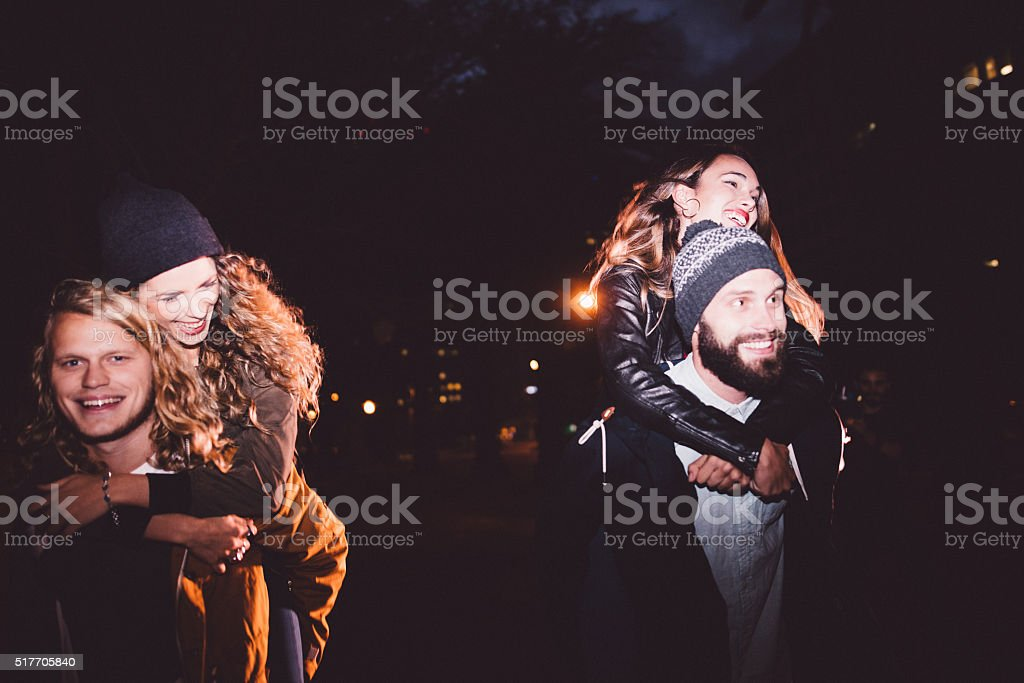 Happy young hipster couples having piggyback rides at night stock photo