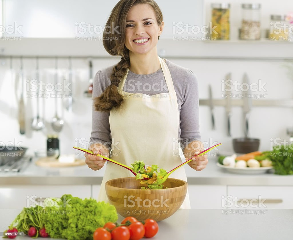 Happy young housewife mixing vegetable salad royalty-free stock photo