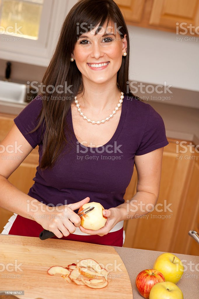 Happy Young Housewife Peeling Apples in Kitchen royalty-free stock photo