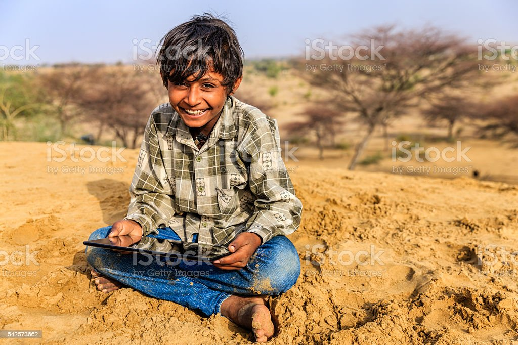 Happy young Indian boy using digital tablet, desert village, India stock photo