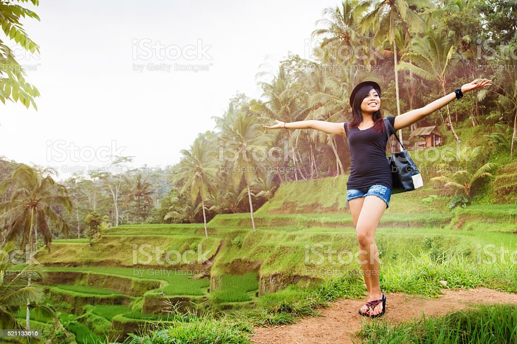 Happy young Indonesian woman proudly shows off Bali landscape stock photo