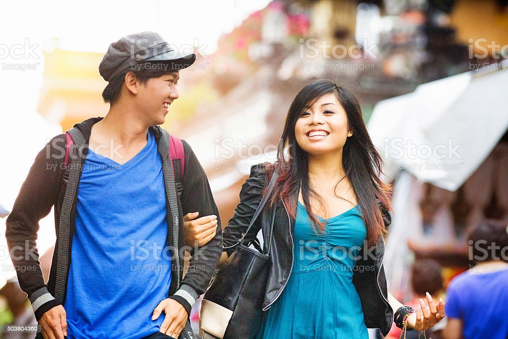 Happy young Indonesian woman shows her male friend Ubud stock photo