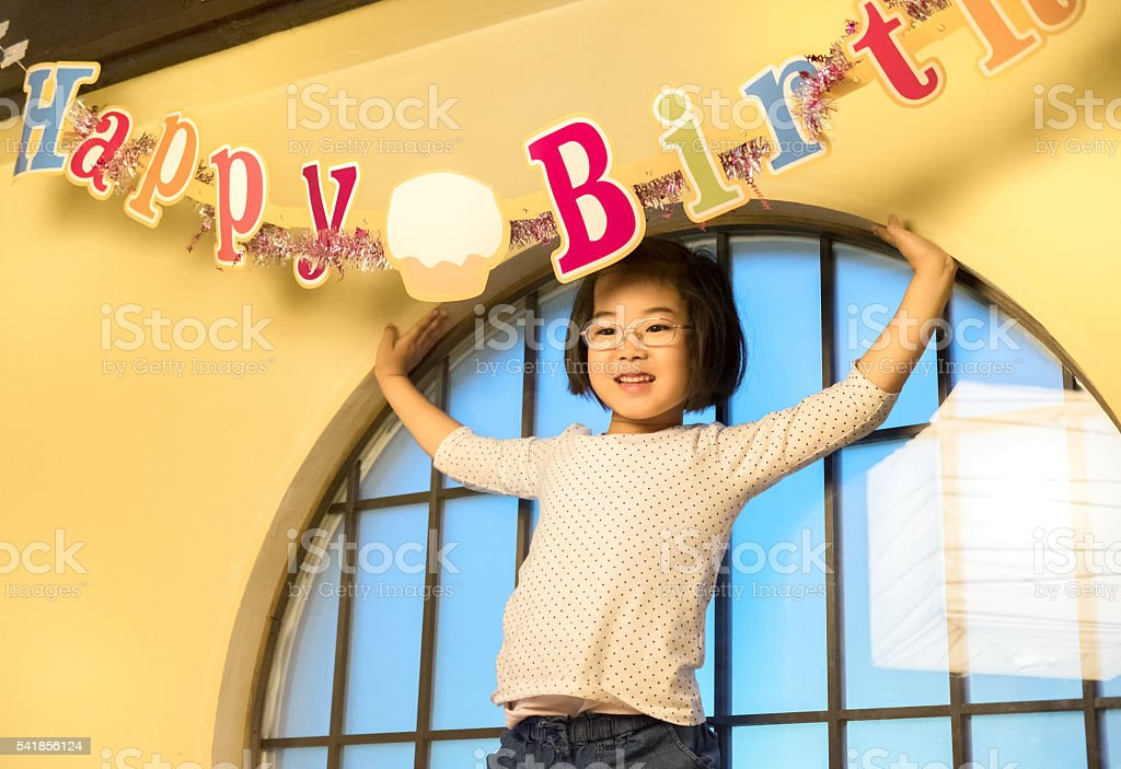 Happy Young Japanese Girl Celebrating Birthday under Banner Decoration Sign stock photo