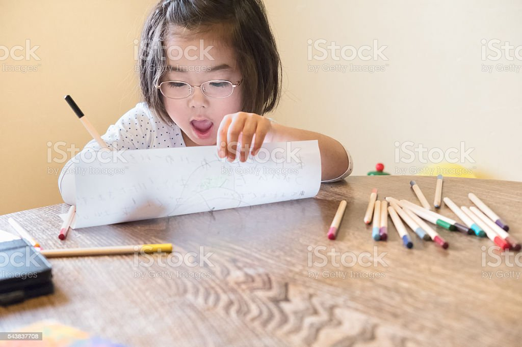 Happy Young Japanese Girl Drawing with Pencil Crayons at Home stock photo