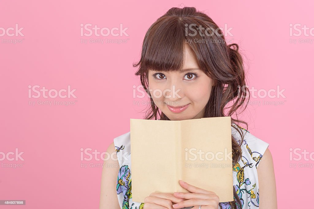 happy young japanese woman reading storybook on couch at home stock photo