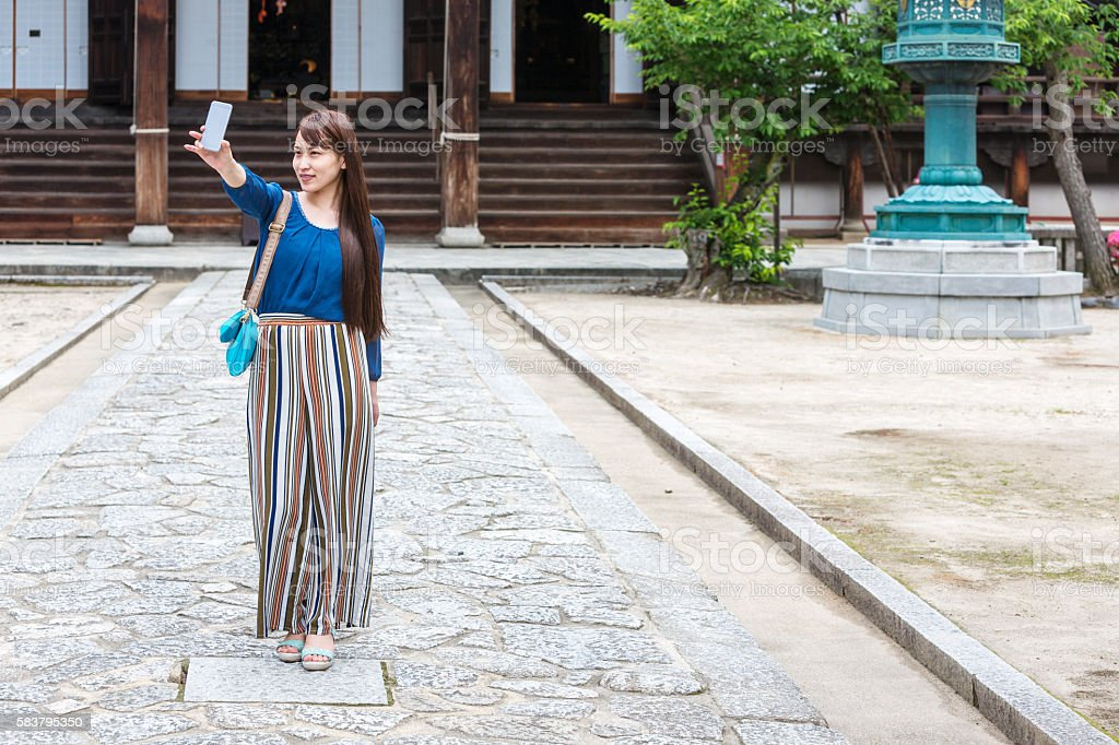 Happy Young Japanese Woman Taking Smartphone Selfie at Buddhist Temple stock photo