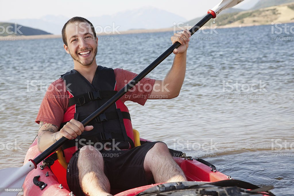Happy young kayaker on a lake in his kayak royalty-free stock photo