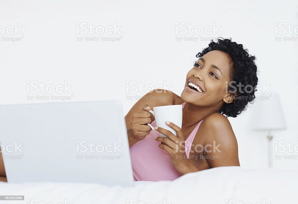 Happy young lady drinking coffee while lying in bed royalty-free stock photo