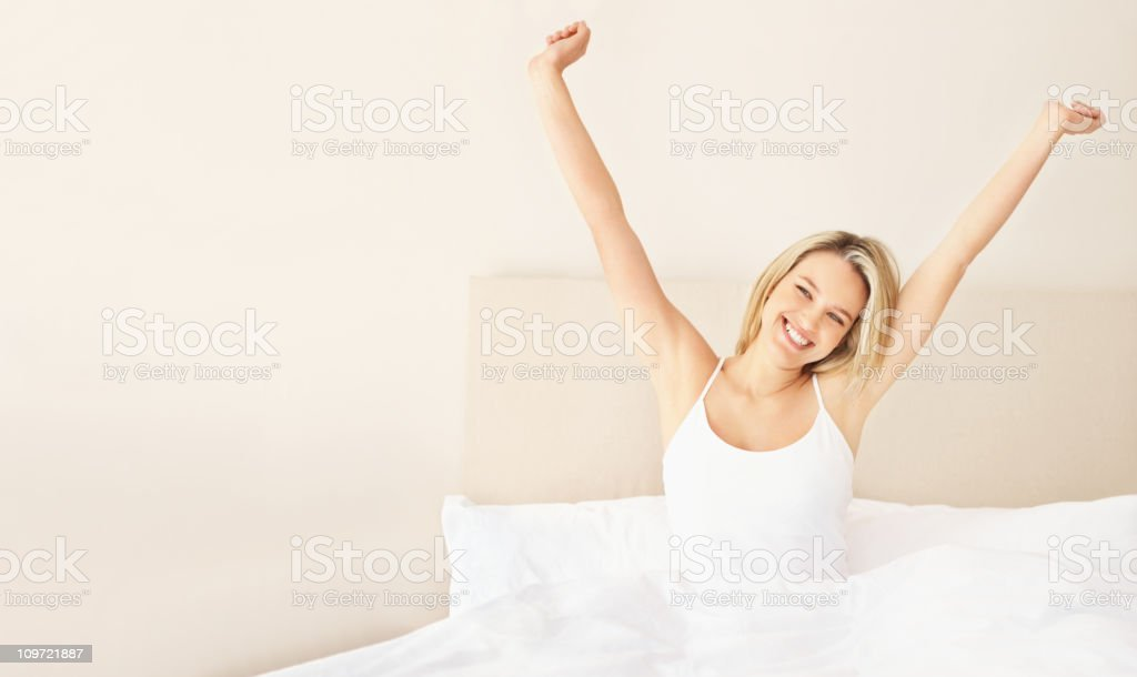 A happy young lady in bed with her hands raised stock photo