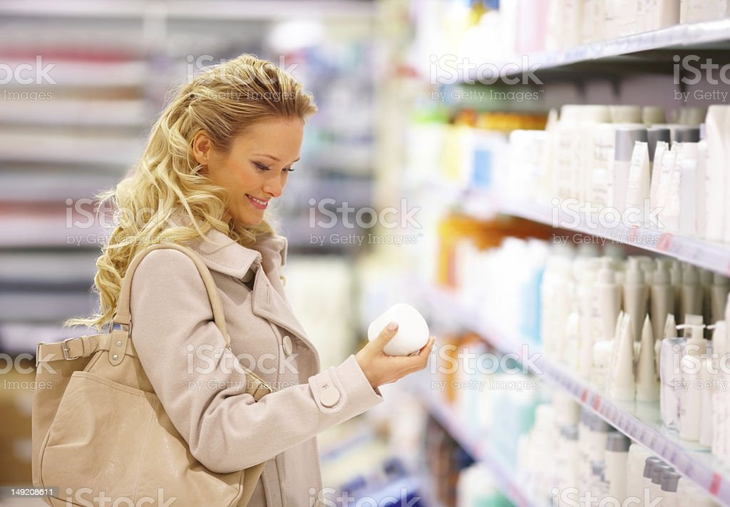 Happy young lady selecting beauty products in mall royalty-free stock photo