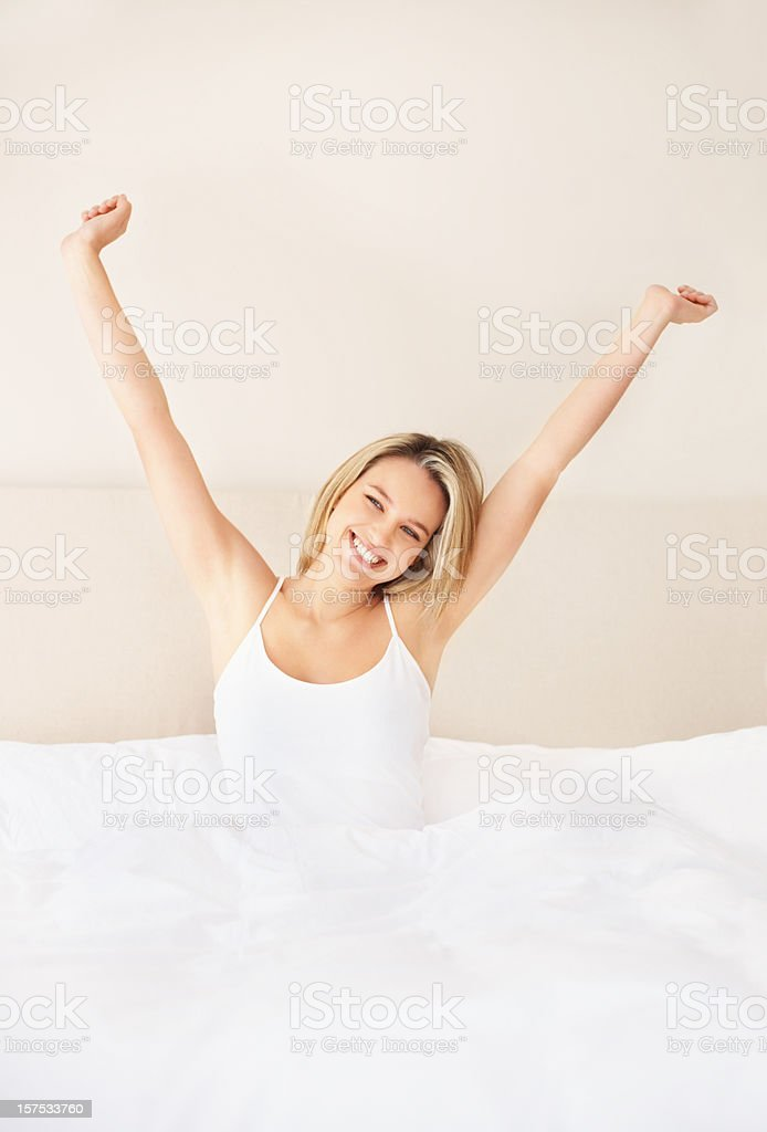 Happy young lady stretching hands in morning on bed royalty-free stock photo