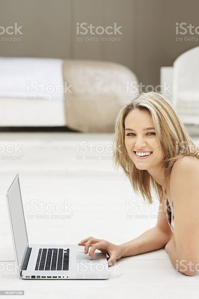 Happy young lady using laptop at home royalty-free stock photo
