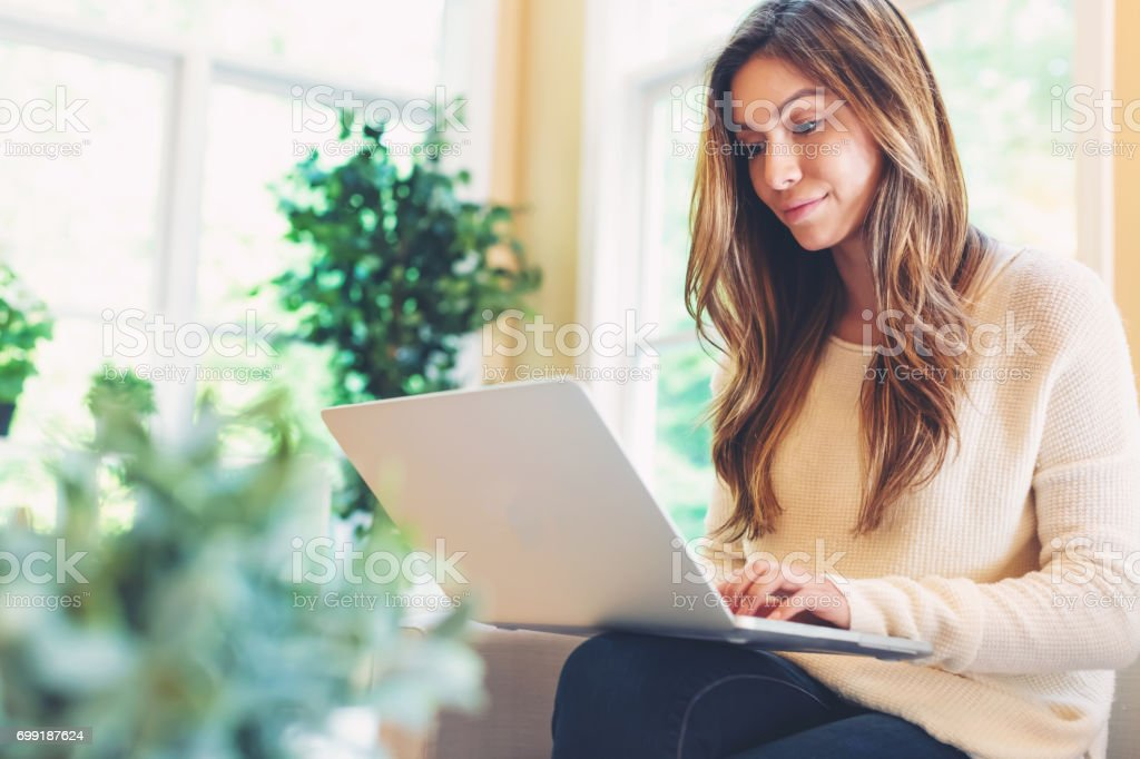 Happy young latina woman using her laptop at home stock photo