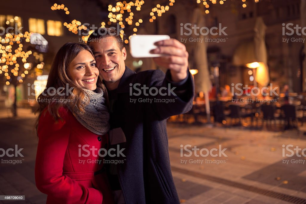Happy young loving couple making selfie and smiling stock photo