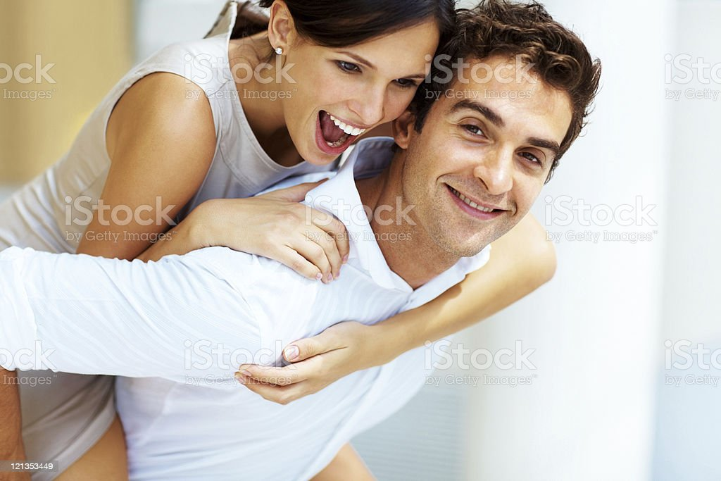 Happy young male giving his girlfriend a piggyback ride royalty-free stock photo