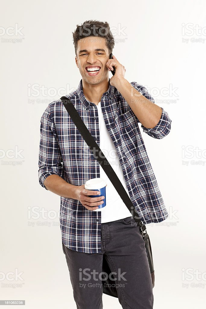 Happy young male student having a conversation on mobile phone royalty-free stock photo