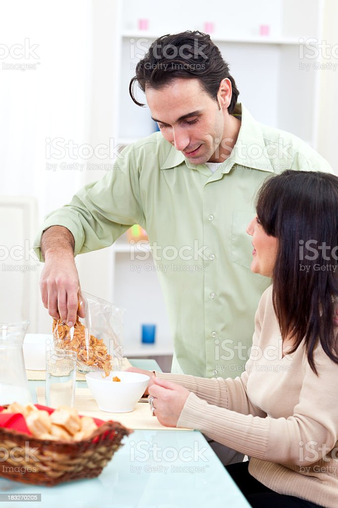 Happy young man and woman having cereals for breakfast royalty-free stock photo