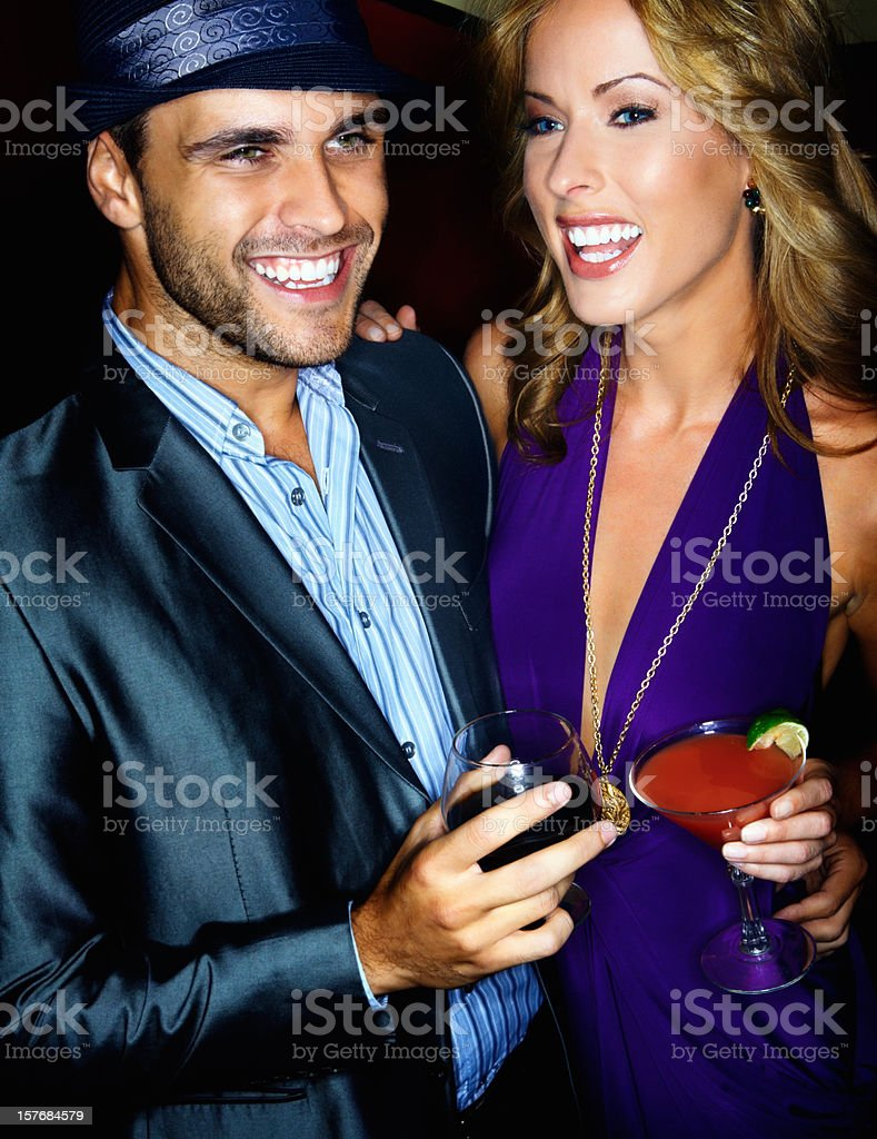 Happy young man and woman having drinks together against black royalty-free stock photo