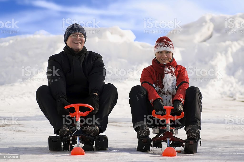 Happy young man and woman riding snowmobiles stock photo