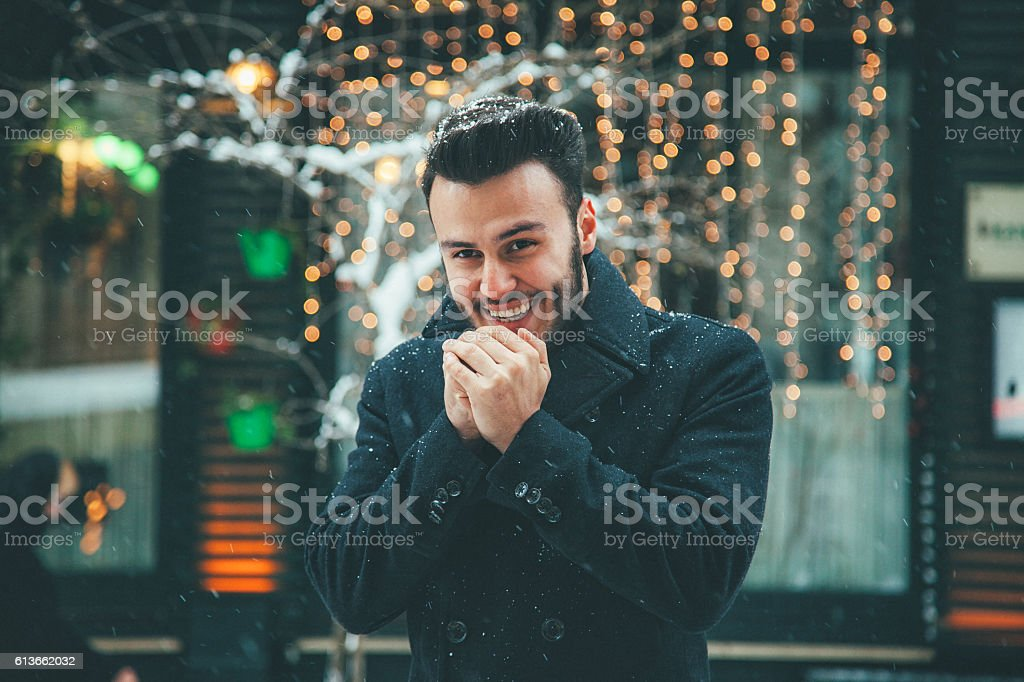 Happy Young man blowing on hands in winter stock photo