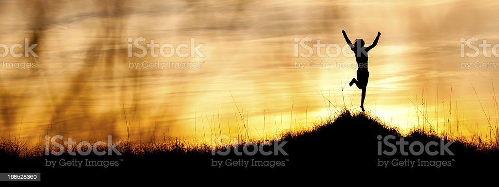 Happy Young man celebrating on a hilltop at sunset royalty-free stock photo