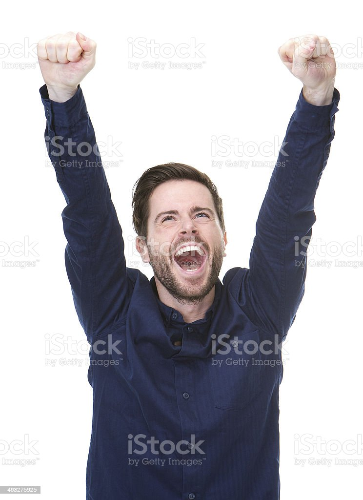 Happy young man celebrating with arms raised stock photo