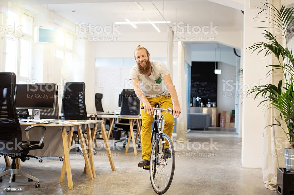 Happy young man cycling in a startup stock photo
