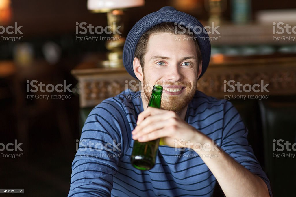 happy young man drinking beer at bar or pub stock photo