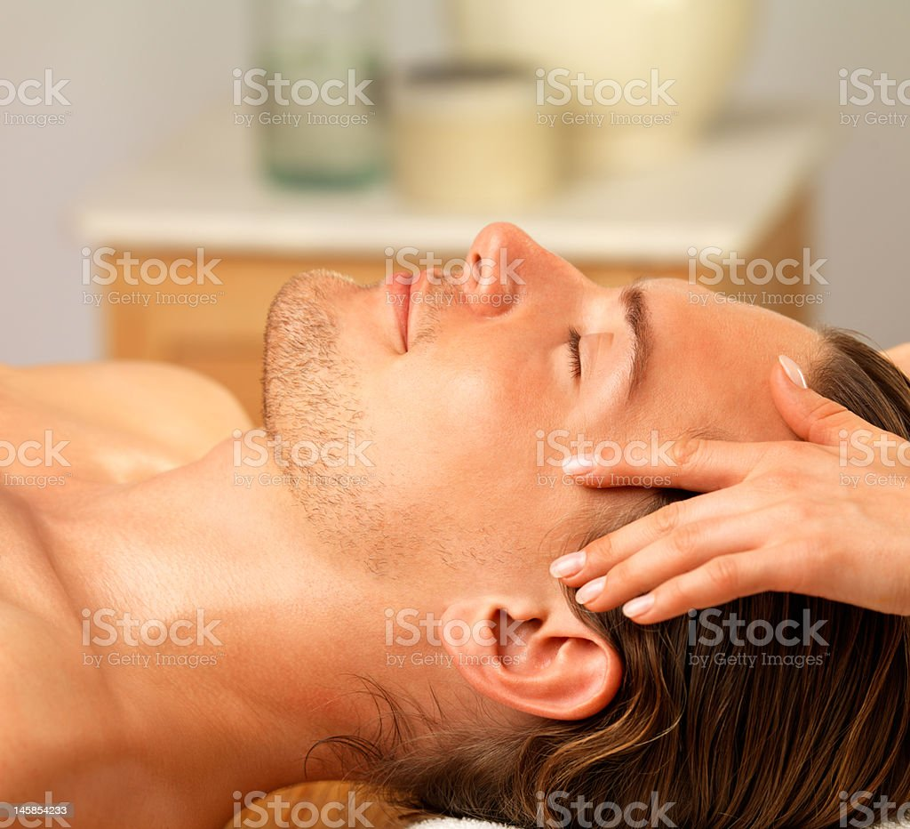 Happy young man getting facial massage on spa holiday royalty-free stock photo