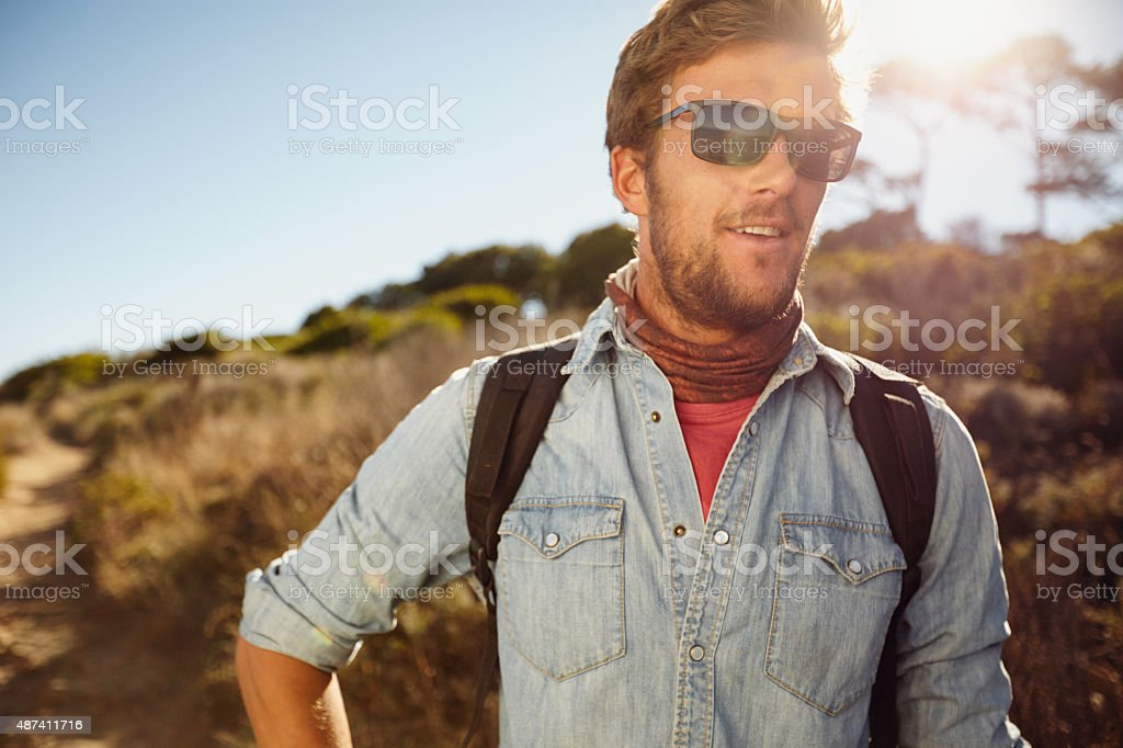 Happy young man hiking in countryside stock photo