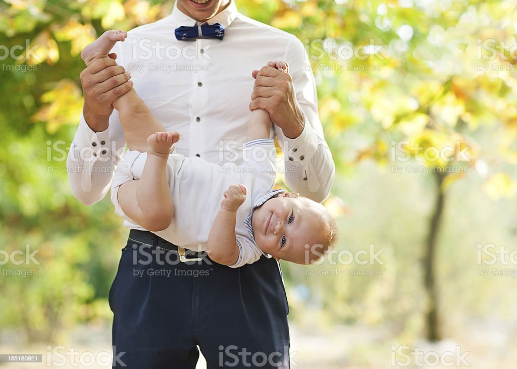 Happy young man holding a smiling 7-9 months old baby royalty-free stock photo