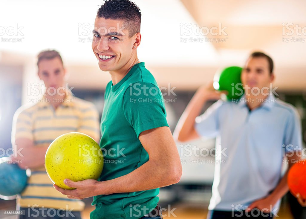 Happy young man holding bowling ball. stock photo