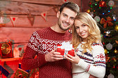 Happy young man holding christmas present with his girlfriend
