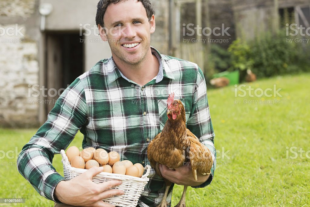 Happy young man holding his chicken and basket of eggs stock photo