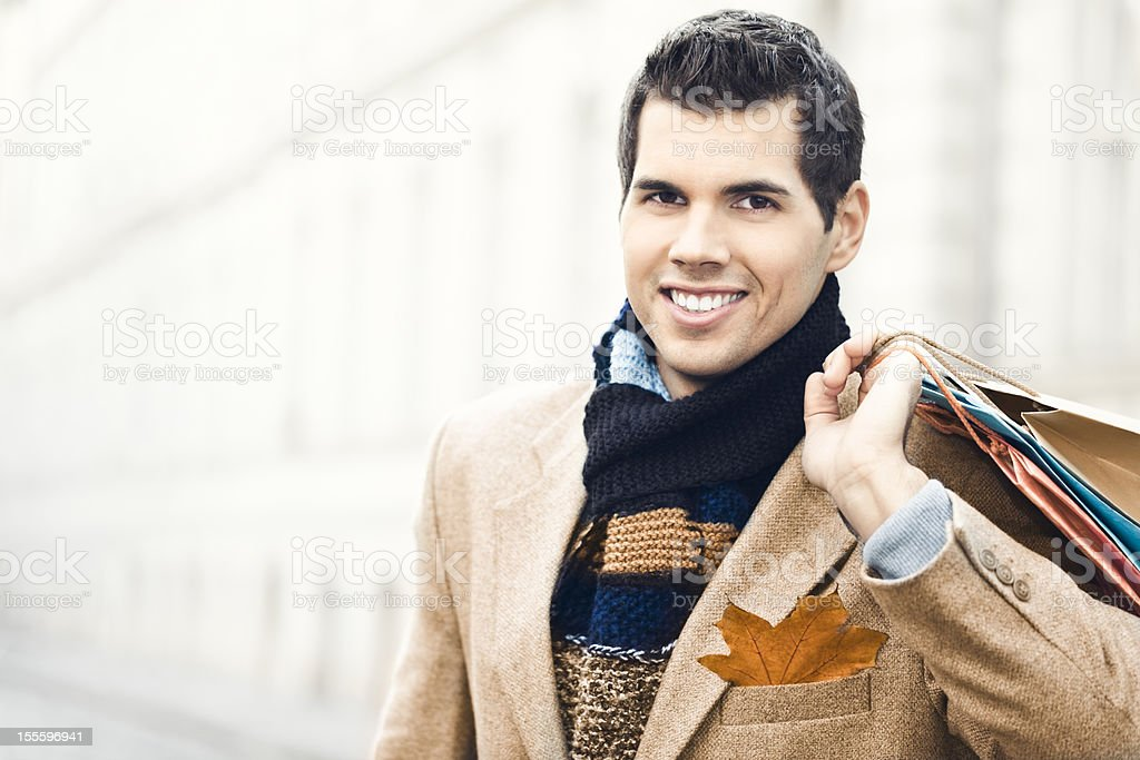 Happy young man holding shopping bags royalty-free stock photo