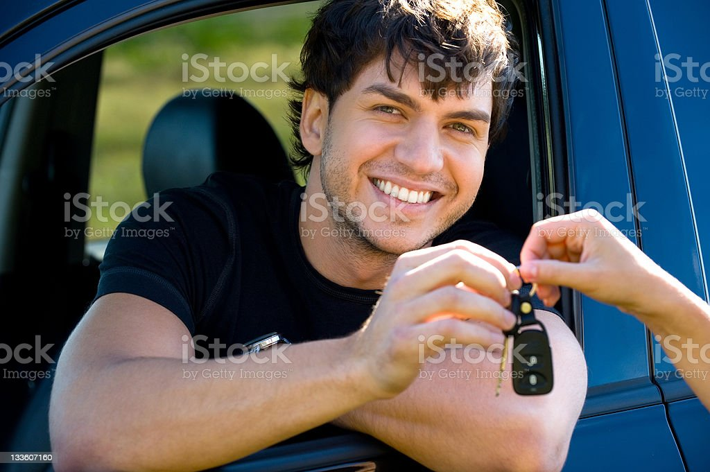 A happy young man holds the keys to a car royalty-free stock photo
