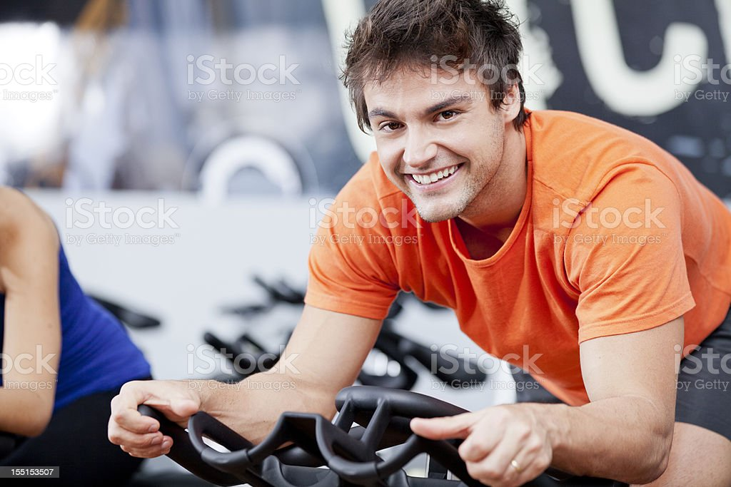 Happy young man in a cycling class royalty-free stock photo