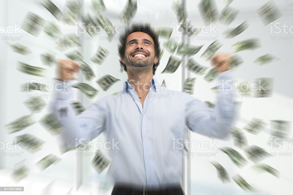Happy young man in a rain of money stock photo