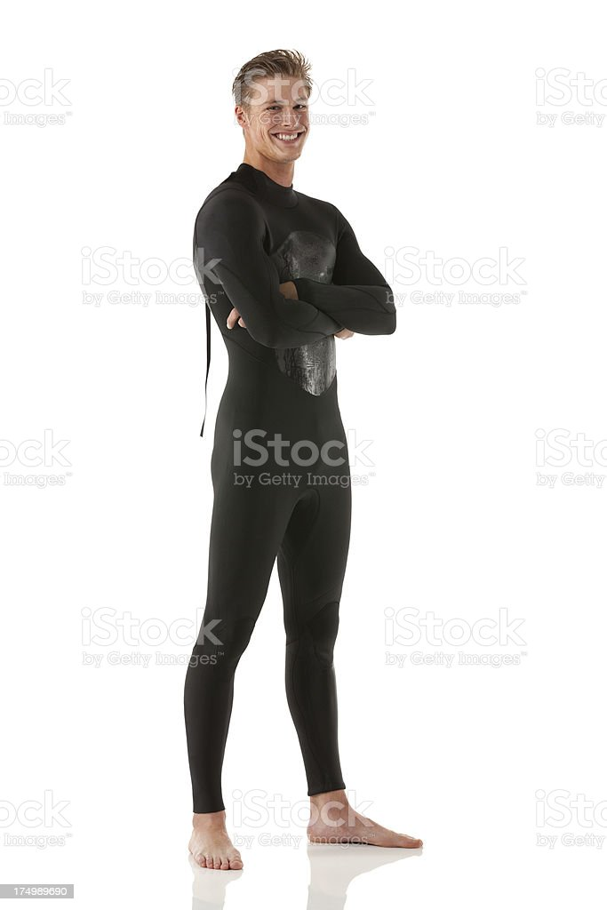 Happy young man in black wet suit. stock photo