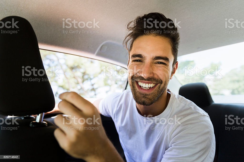 Happy young man in car stock photo