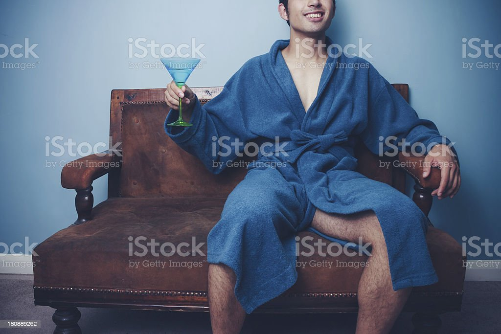 Happy young man in dressing gown drinking martini royalty-free stock photo