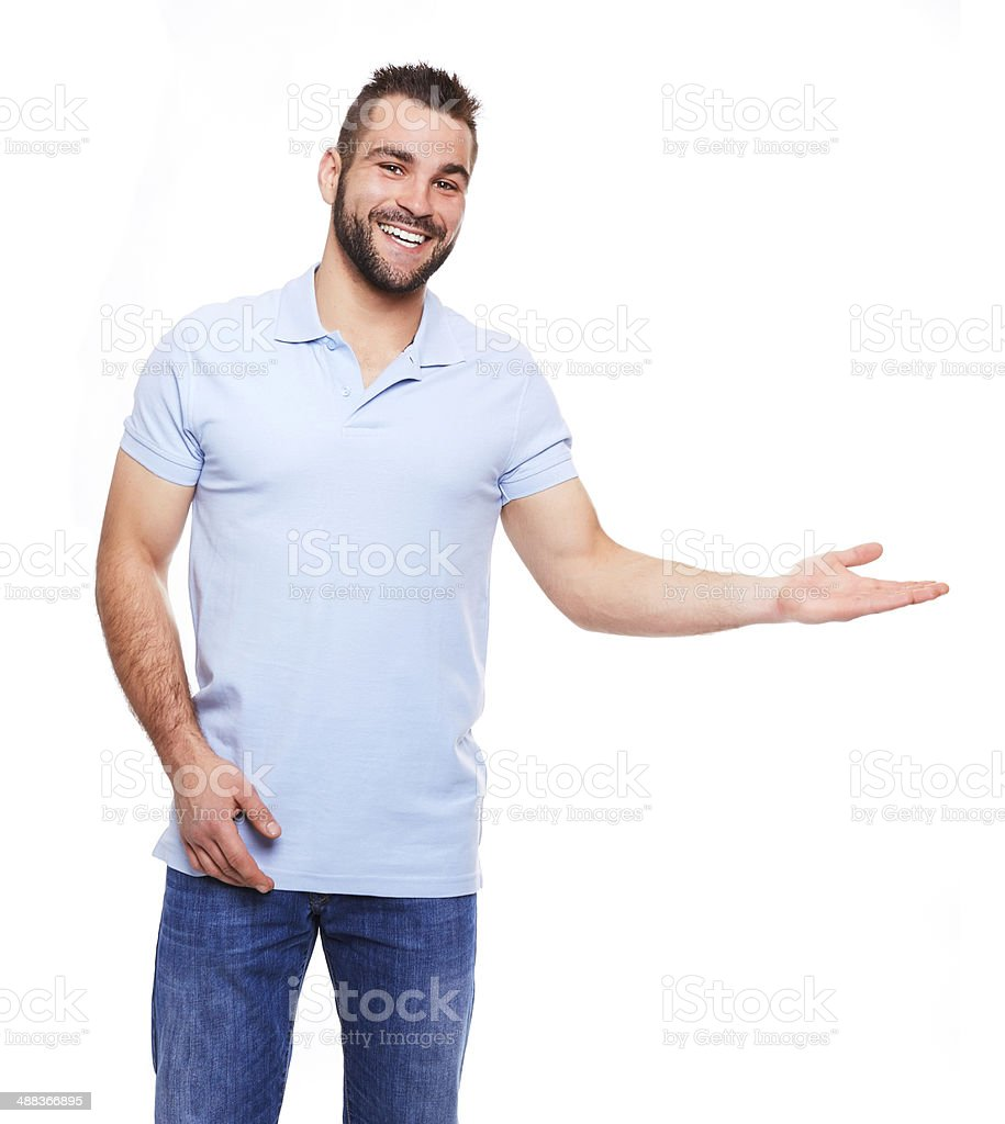 Happy young man in polo shirt showing empty copyspace stock photo