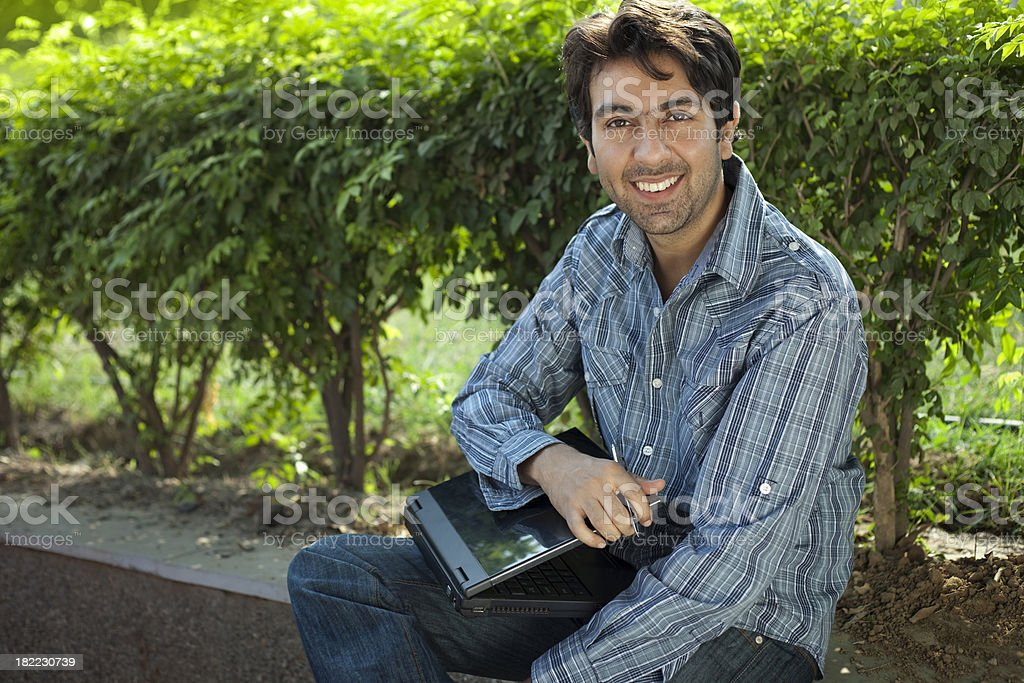 Happy young man is looking at camera holding a laptop. royalty-free stock photo