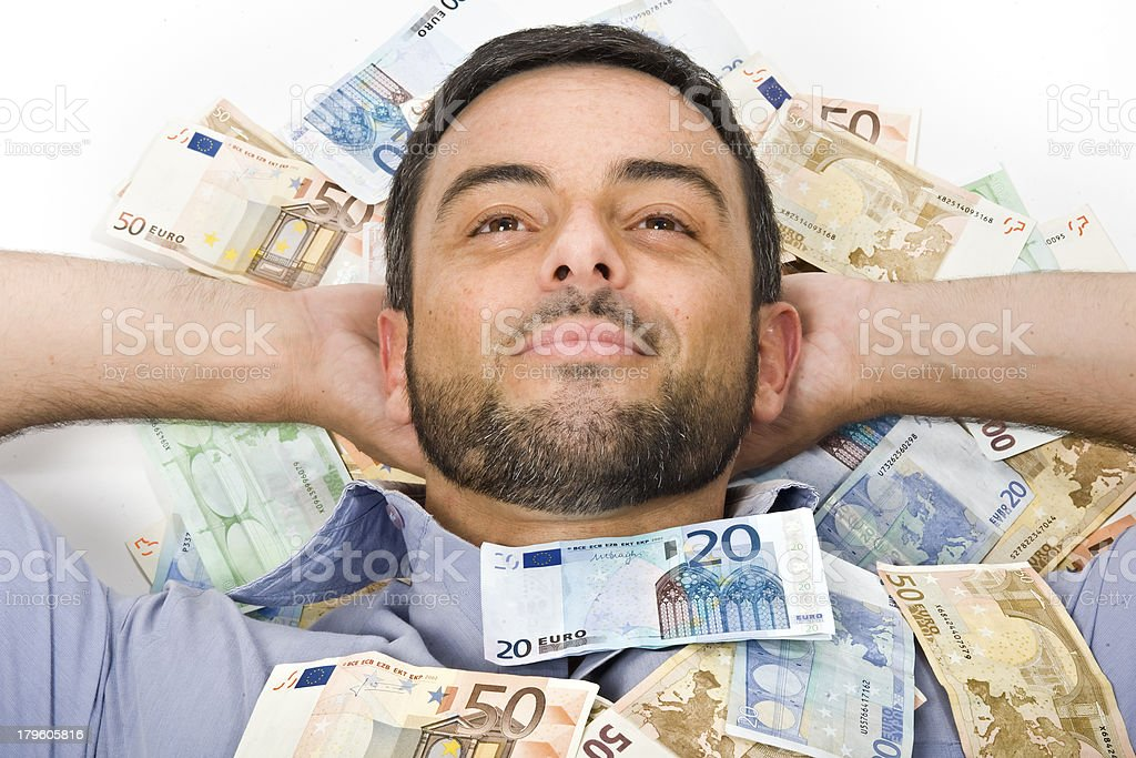 Happy Young Man laying on Banknotes royalty-free stock photo