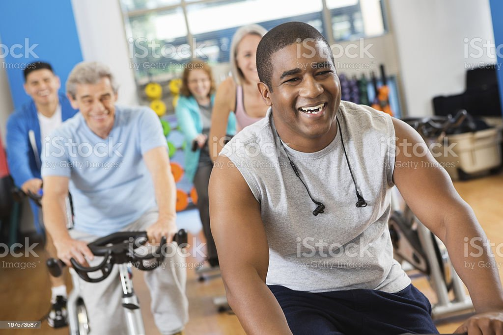 Happy young man leading his fitness club's cycling class royalty-free stock photo