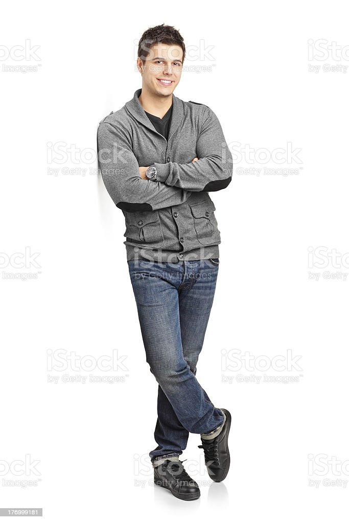Happy young man leaning against wall stock photo