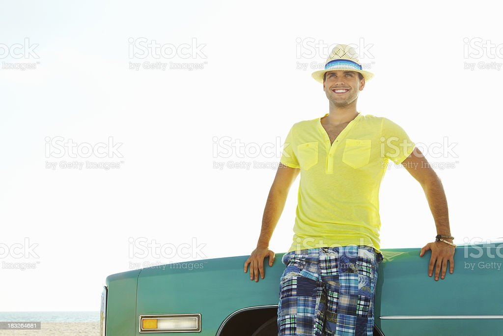 Happy young man leaning on his Cadillac car - copyspace royalty-free stock photo