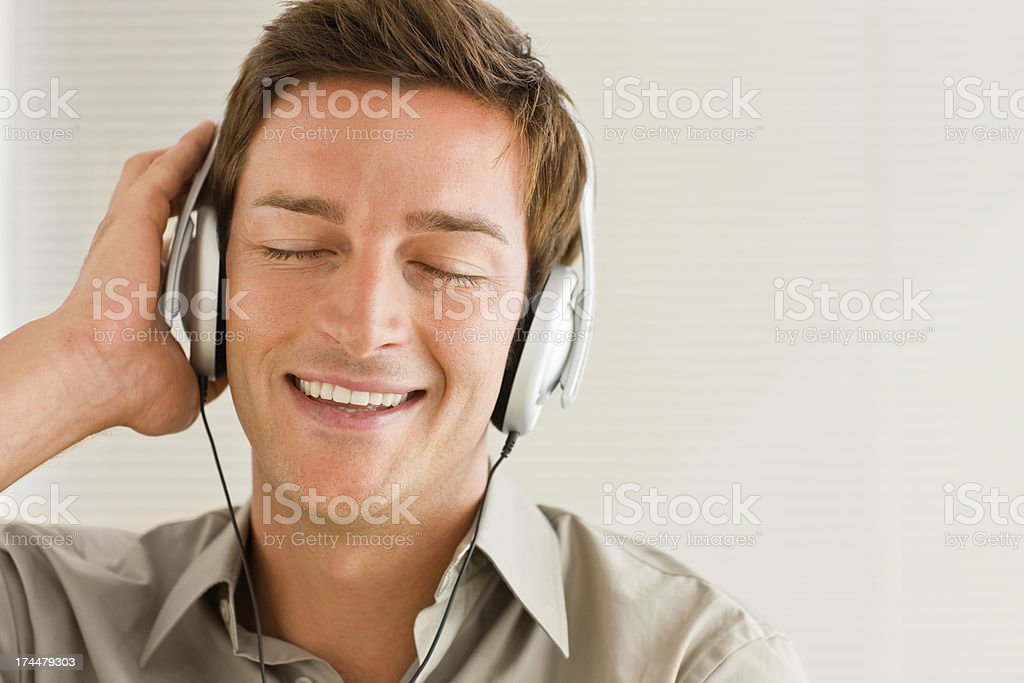 Happy young man listening music royalty-free stock photo