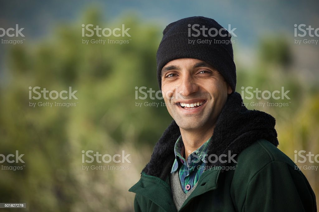 Happy young man looking at camera in winter outdoor scene. stock photo
